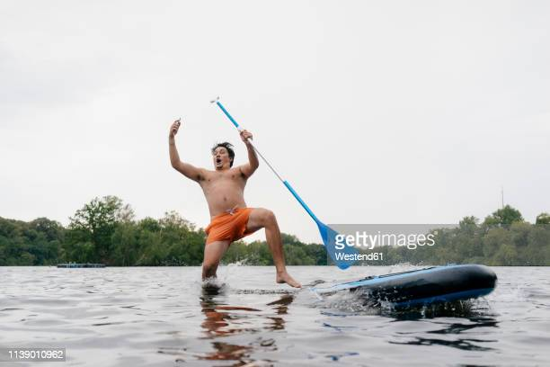 man falling from sup board while taking a selfie - falling stock pictures, royalty-free photos & images