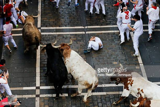 A man falls as revellers run with Fuente Ymbro's fighting bulls entering Estafeta Street during the second day of the San Fermin Running of the Bulls...