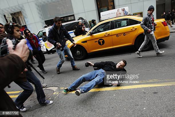 A man falls down as NYPD officers try to arrest protesters while they take part in demonstrations against Republican presidential candidate Donald...