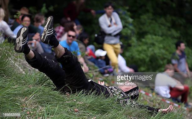 A man falls down the steep gradient of Cooper's Hill during the annual Bank Holiday tradition of cheeserolling on May 27 2013 in Brockworth...