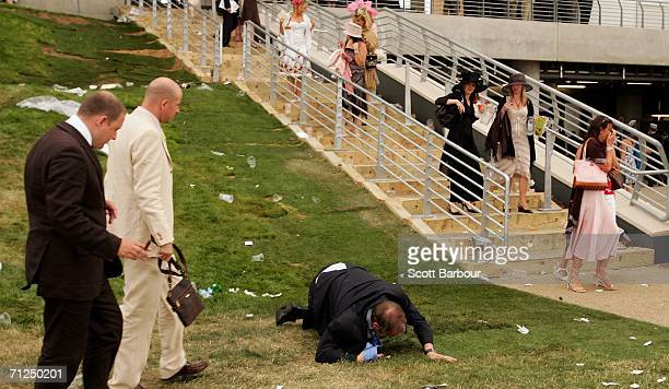 A man falls over as racegoers walk past him on the first day of Royal Ascot at the Ascot Racecourse on June 20 2006 in Ascot England The event has...