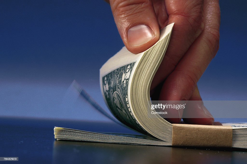 Man fanning bundle of dollar bills : Stockfoto