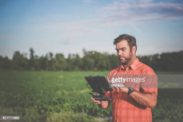 man farmer pilot using drone remote controller at sunset - remote controlled stock photos and pictures