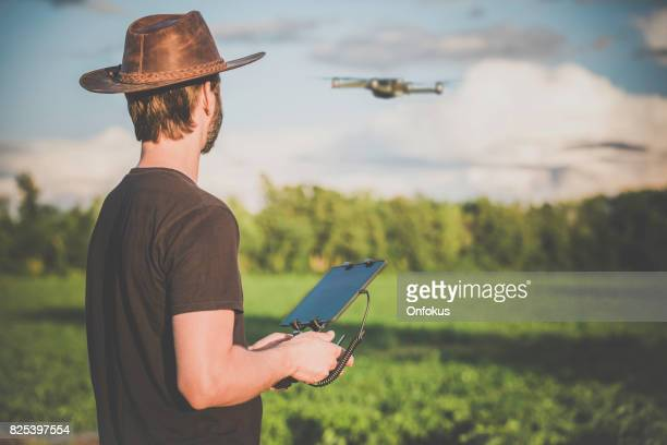 Man Landwirt-Pilot mit Drone Fernbedienung bei Sonnenuntergang