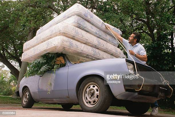 Man fastening four mattresses to roof of car