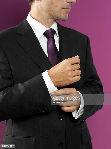 A man fastening his cufflink