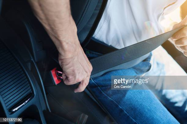 man fastening seatbelt - fastening stock pictures, royalty-free photos & images