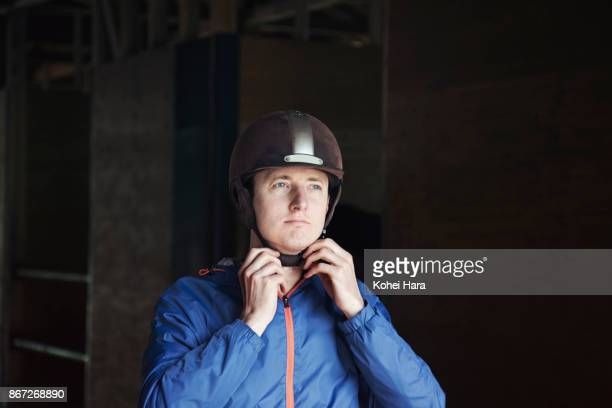 man fastening the belt of a helmet and preparing for horse riding - riding hat stock pictures, royalty-free photos & images