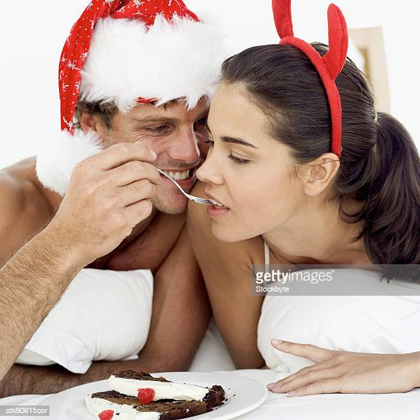 man feeding a woman Christmas cake