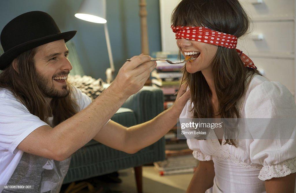 Man feeding blindfolded woman, smiling : Stock Photo