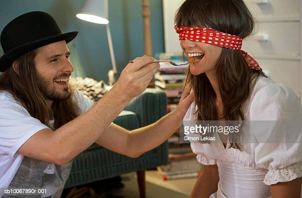 Man feeding blindfolded woman, smiling