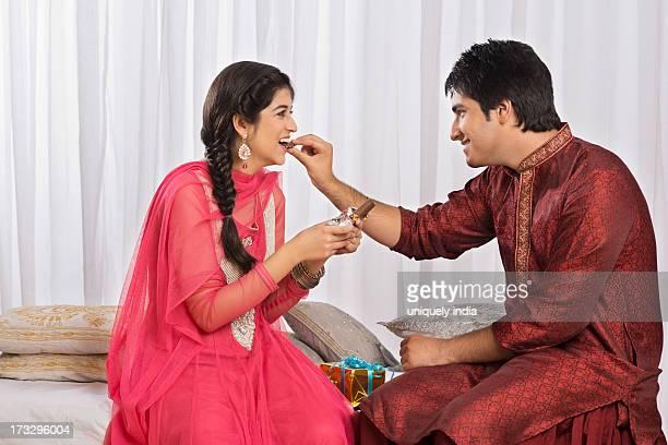 Man feeding chocolate to his sister at Raksha Bandhan