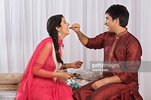 man feeding chocolate to his sister at raksha bandhan - raksha bandhan stock photos and pictures