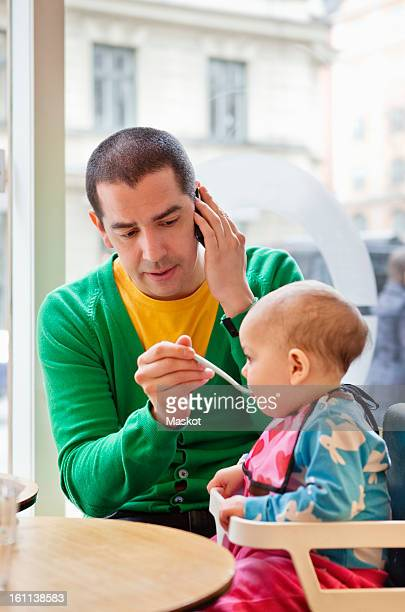 man feeding daughter (0-11 months) and talking in phone - 0 11 monate stock-fotos und bilder