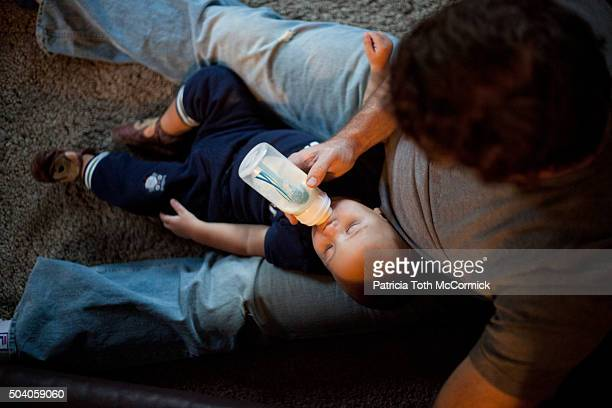 man feeding infant boy a bottle - baby bottle stock pictures, royalty-free photos & images