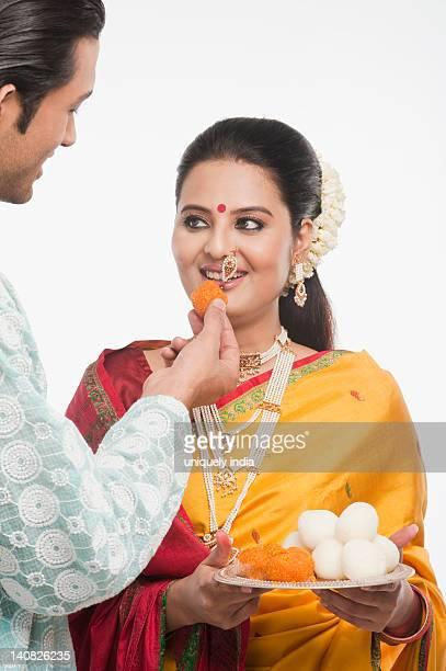 Man feeding prasad to a woman on Gudi Padwa festival