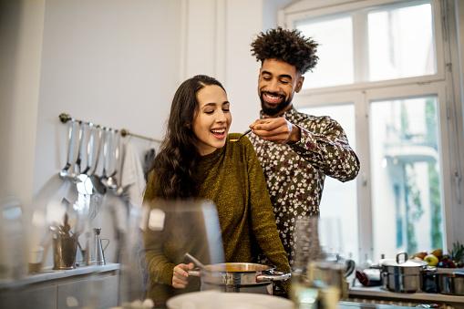 Man feeding pumpkin soup to girlfriend in kitchen - gettyimageskorea