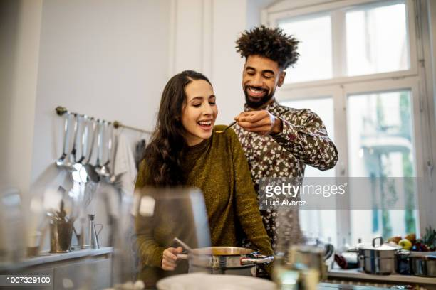 man feeding pumpkin soup to girlfriend in kitchen - heteroseksueel koppel stockfoto's en -beelden