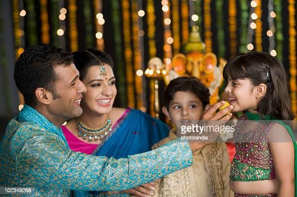 Man feeding sweets to his children on Diwali
