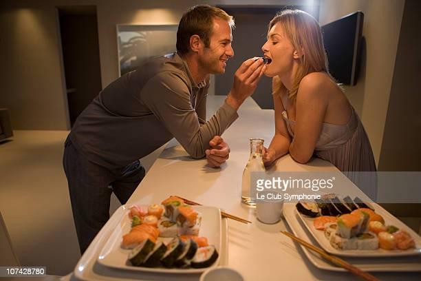 Man feeding wife sushi