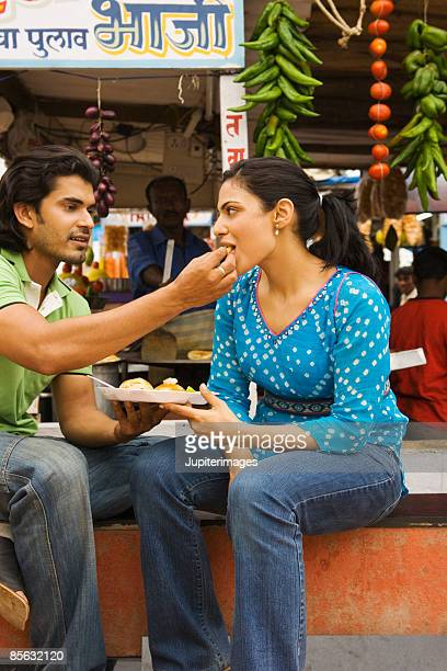 Man feeding woman pau bhajji, India
