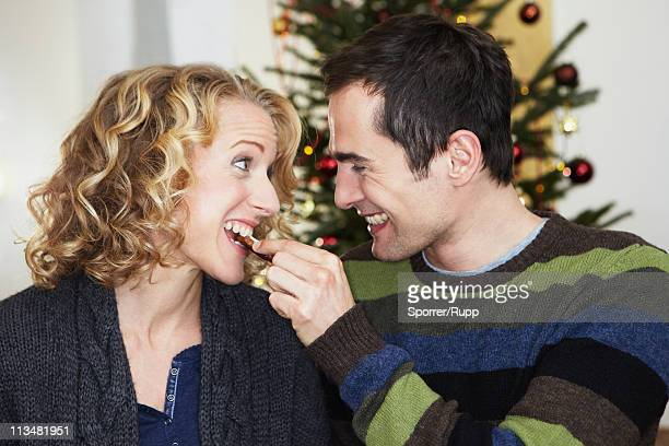 Man feeding woman with cookie