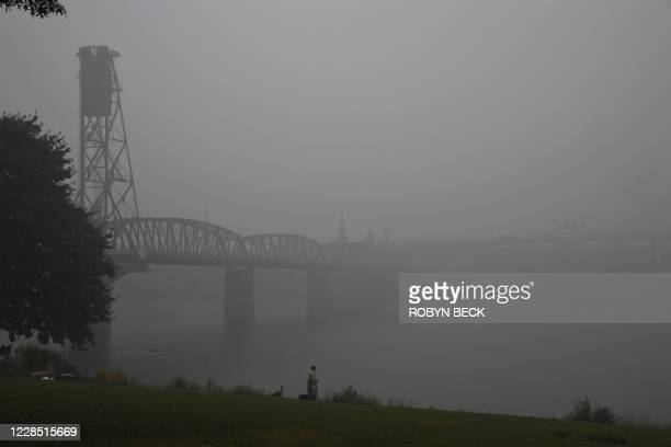 Man feeds ducks along the banks of the Williamette River in downtown Portland, Oregon where air quality due to smoke from wildfires was measured to...