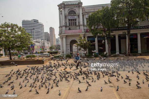 A man feeds pigeons in the deserted commercial hub Connaught Place during a oneday nationwide Janata curfew imposed as a preventive measure against...