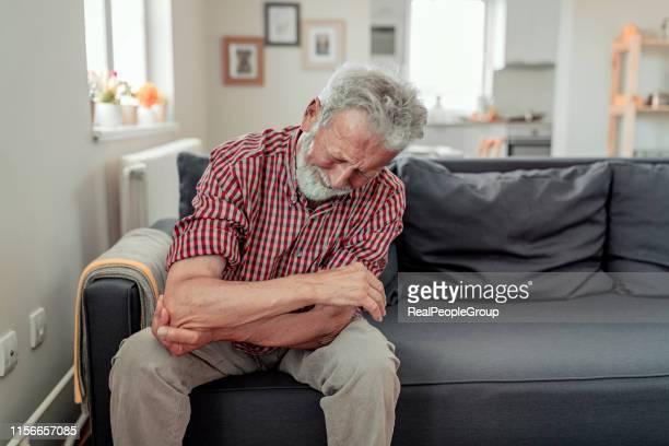 man feeling elbow pain, sport injury, chronic rheumatism, health problem - rheumatism stock pictures, royalty-free photos & images