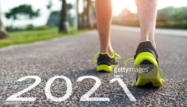 man feet and number 2021 on the road - new year stock pictures, royalty-free photos & images