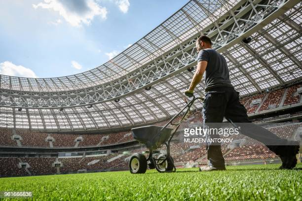 A man fertilises the grass on the pitch of the Luzhniki Stadium in Moscow on May 23 2018 The 80000seater stadium will host seven World Cup matches...