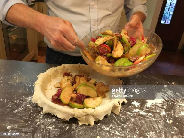 Man filling apples and walnuts into a not yet baked apple pie