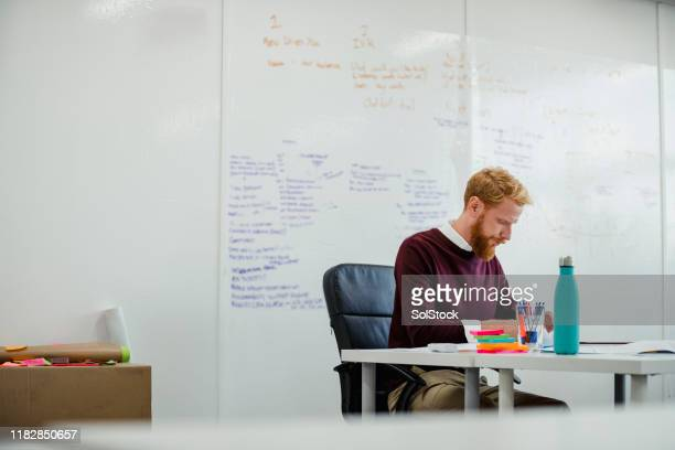 man filling out paperwork - creative director stock pictures, royalty-free photos & images