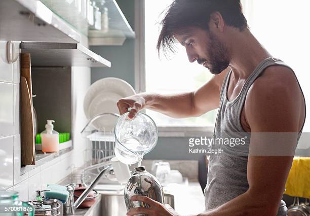 man filling siphon with water - tank top stock pictures, royalty-free photos & images