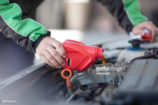 man filling up car with motor oil - oil change stock pictures, royalty-free photos & images