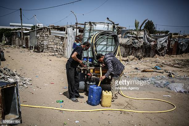 Man fills a bucket with water brought by a water tank carriage as Palestinians face a water crisis in Gaza City, Gaza on May 9, 2016. Palestinians...