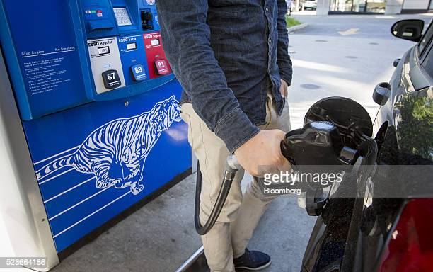 A man fills a car with fuel at an Esso gas station in Vancouver British Columbia Canada on Friday May 6 2016 The worst wildfire in Alberta history is...