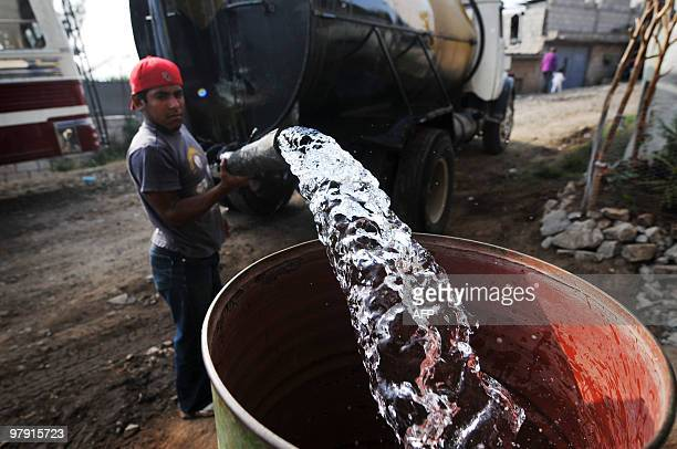 A man fills a drum with potable water from a tanker in Villa Nueva 22 km south of Guatemala City on March 20 on the eve of the celebration of the...