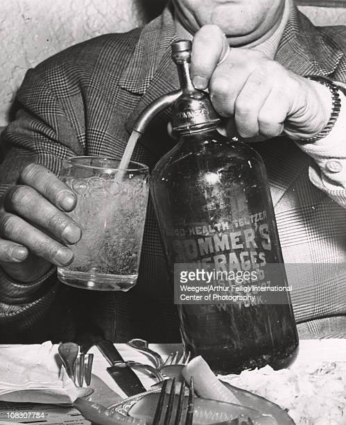 A man fills a glass from a bottle of 'Good Health Seltzer Sommer's Beverages Registered Conents 26 Oz New York' in the foreground is a plate of...