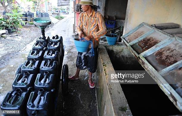 A man fills a jerry can with clean water on World Water Day March 22 2014 in Surabaya Indonesia World Water Day recognizes the global need for water...