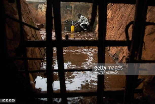 A man fills a jug with water at a water distribution point in the Naguru Go Down slum in Kampala on March 21 2008 The United Nations has declared...