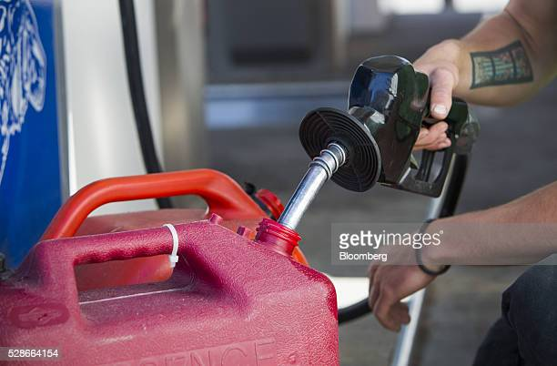 A man fills containers with fuel at an Esso gas station in Vancouver British Columbia Canada on Friday May 6 2016 The worst wildfire in Alberta...