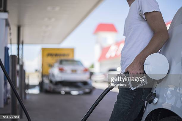 A man fills his car with fuel at a roadside Exxon gas station outside Aurora New Mexico US on Tuesday July 26 2016 Exxon Mobil Corp is scheduled to...