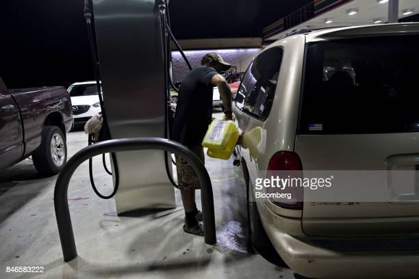 A man fills his car with fuel given to him by another motorist at a gas station that didn't have power to operate the pumps in Estero Florida US on...