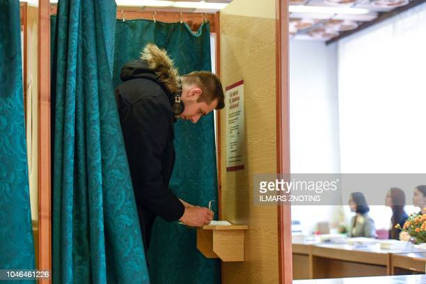 A man fills out his ballot papers at a polling station in Ogre Latvia during general elections on October 6 2018