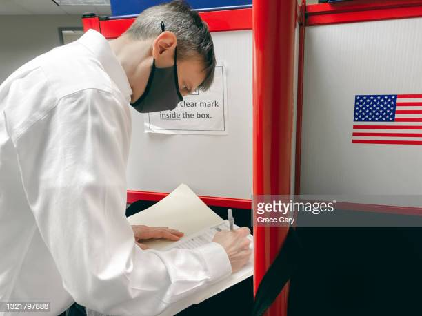 man fills out voting ballot at polling place - midterm election stock pictures, royalty-free photos & images