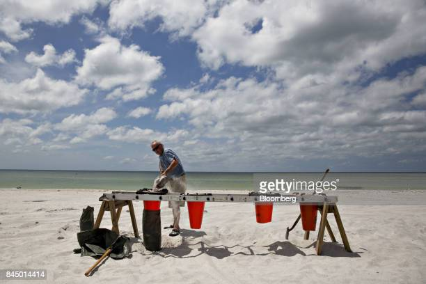 A man fills sandbags at Madeira Beach Park ahead of Hurricane Irma in Madeira Beach Florida US on Saturday Sept 9 2017 Hurricane Irma shifted track...