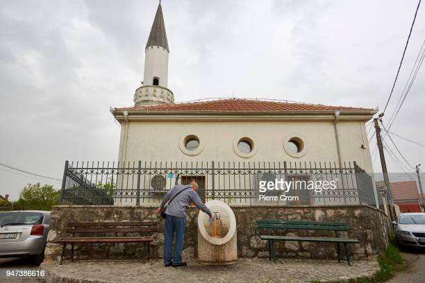 A man fills water bottle outside a mosque in the old town of podgorica on April 17 2018 in Podgorica Montenegro