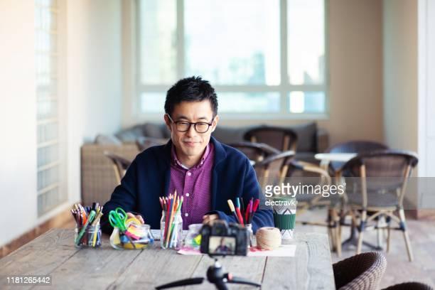 芸術や工芸品のチュートリアルを撮影する男 - 説明書き ストックフォトと画像