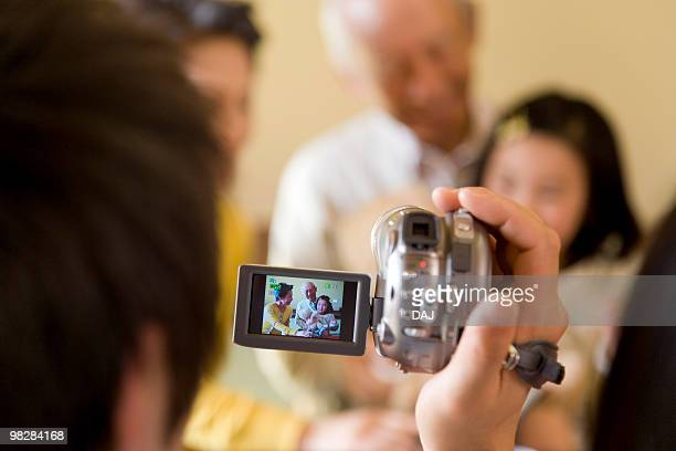 Man filming his family, differential focus